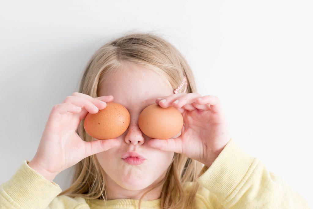 Enfant cachant ses yeux avec des oeufs