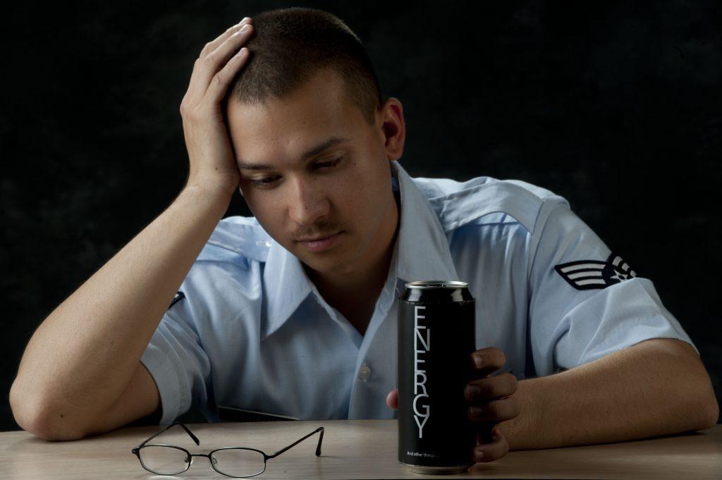 Un homme fatigué en train de boire une boisson énergisante