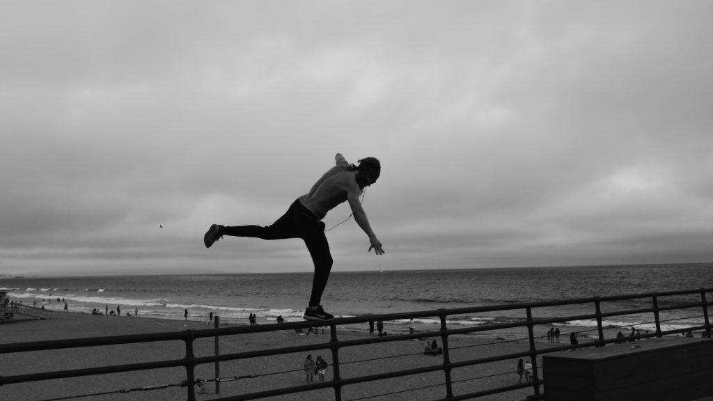 Homme qui se tient en équilibre au bord de la mer