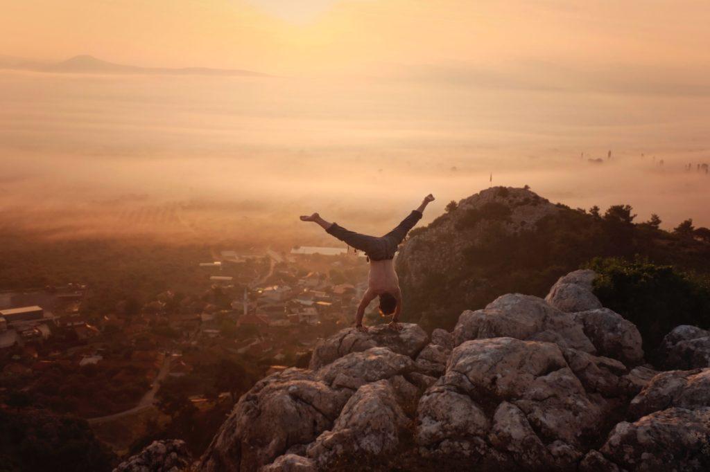 Yogi qui fait un équilibre sur ses mains au bord d'une falaise pendant un couché de soleil