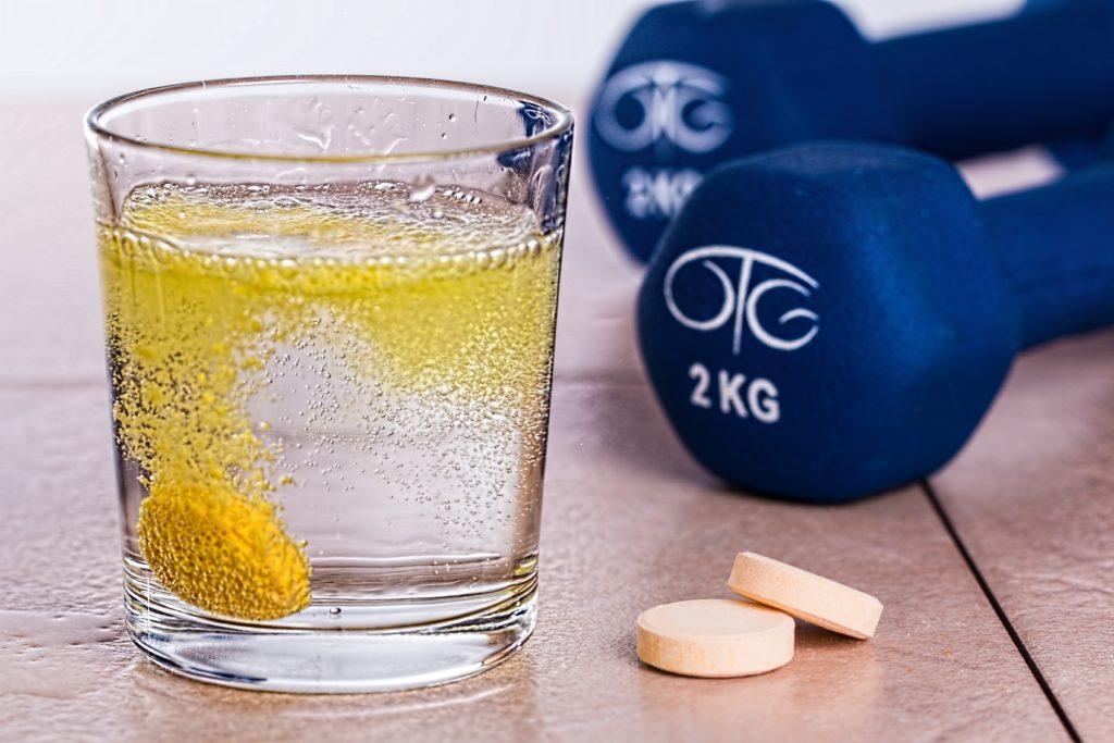 verre d'eau avec pastille à coté de poids de musculation